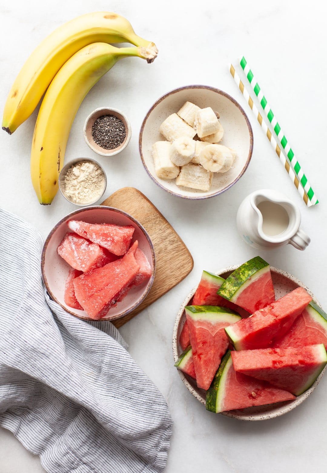 ingredients for watermelon banana smoothie on a white marble board