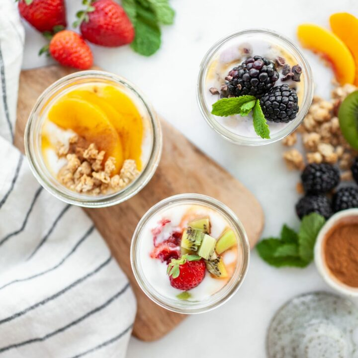 Overhead shot of 3 yogurt recipes in jars with fruit