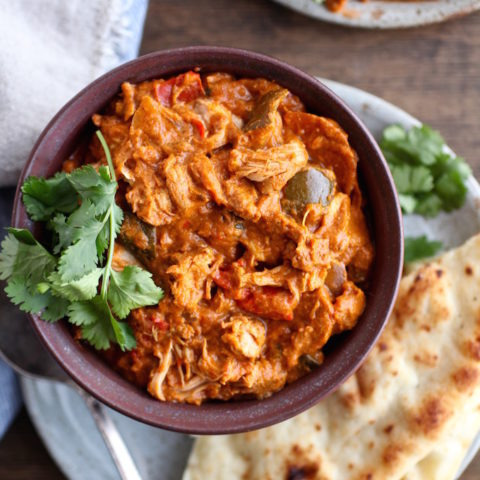 Delicious gluten free dairy free Slow Cooker Indian Butter Chicken in a bowl with naan bread on the side