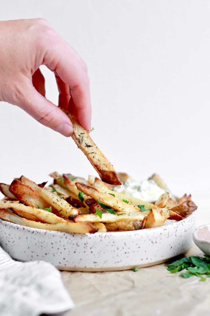 Dipping French fries that are homemade and healthy into herb aioli