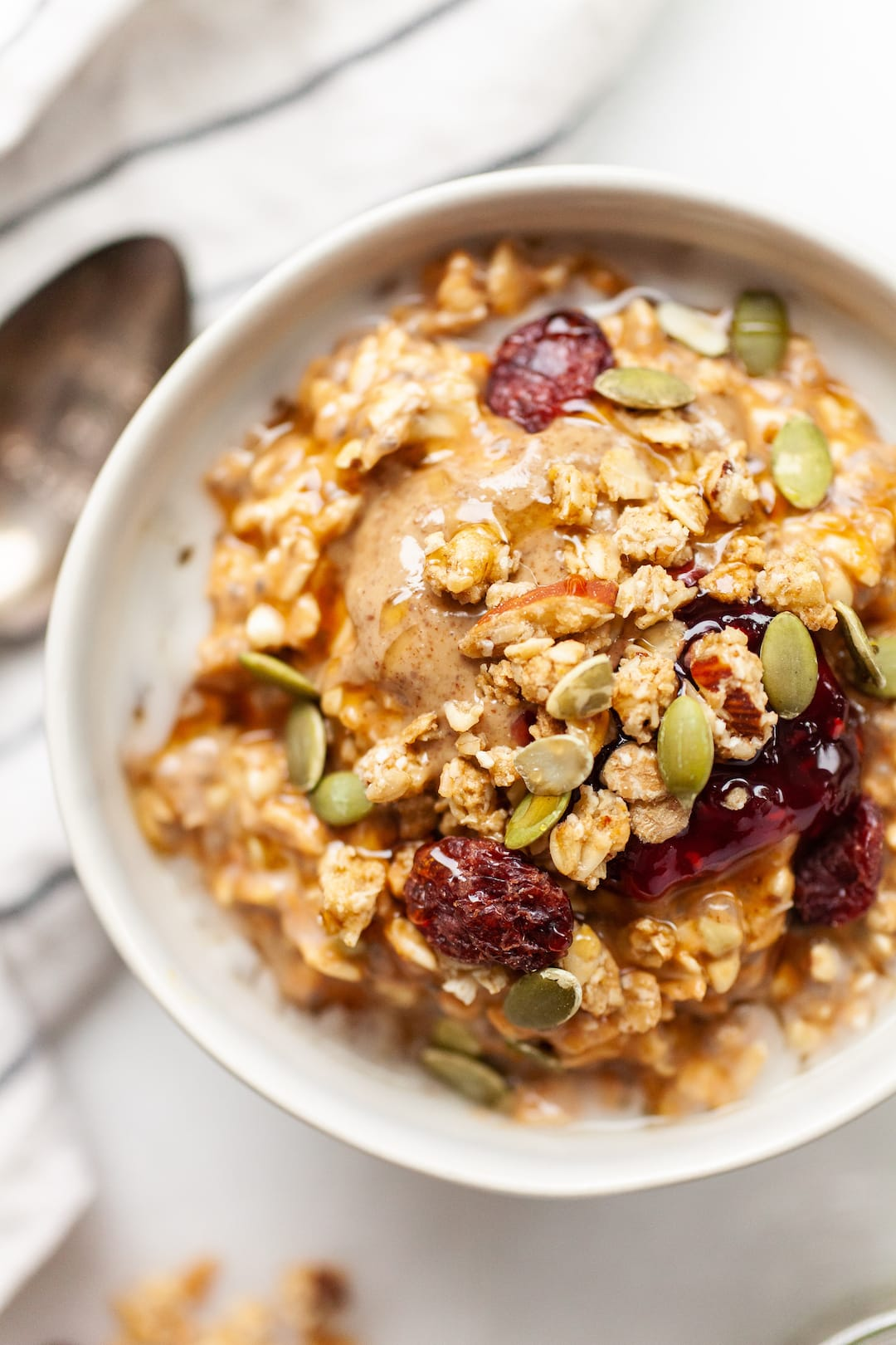 Close up of a bowl of Pumpkin Spice Overnight Oats topped with almond butter, jam, and granola