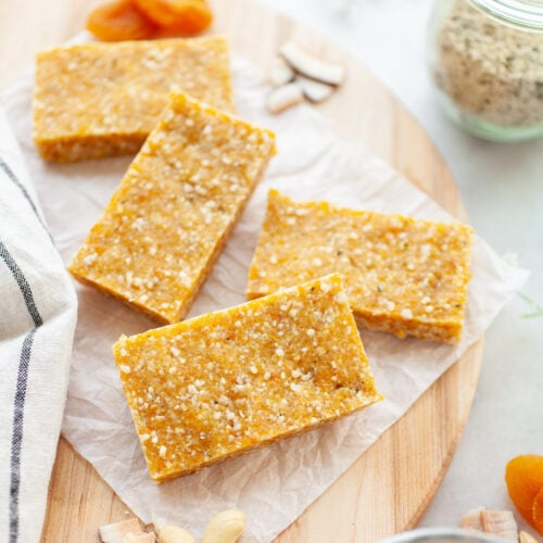 Apricot Cashew Energy Bars on a wood board with apricots