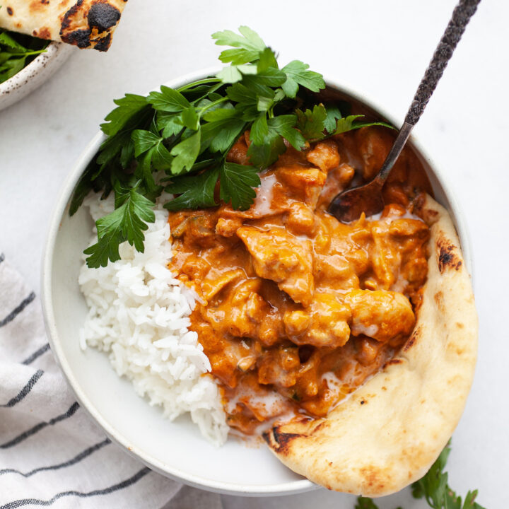 Dairy free butter chickening a bowl with rice, naan, and fresh herbs