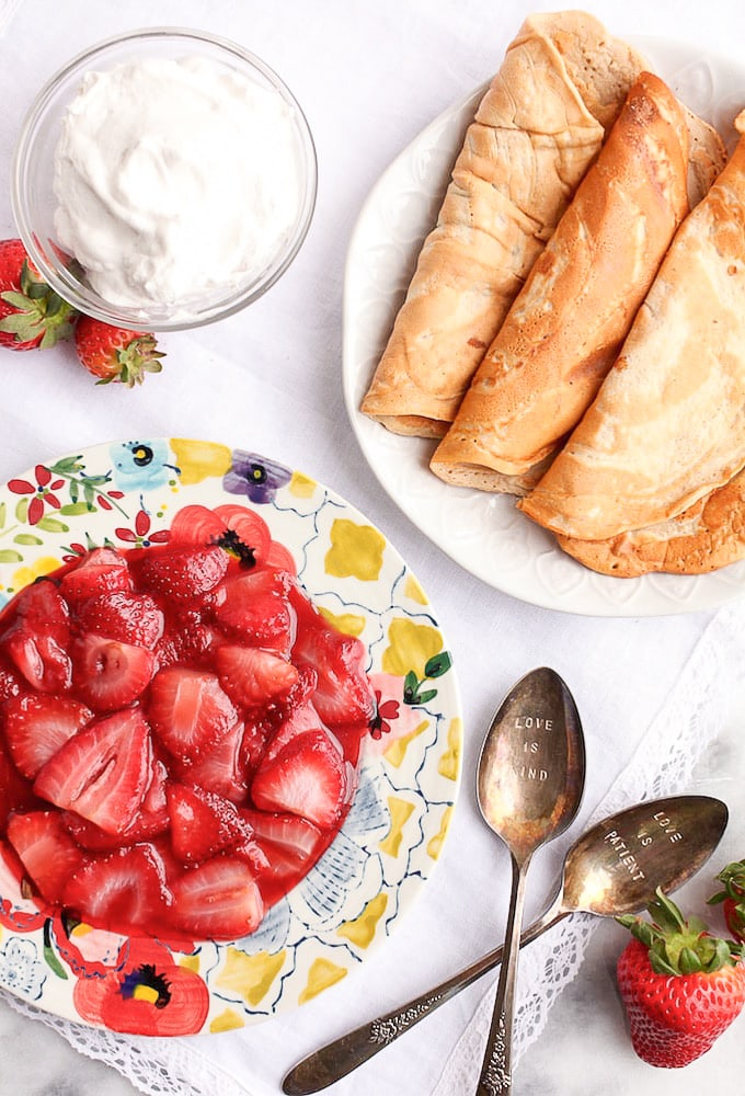 Healthy Protein Crepes on a plate with another plate with strawberry filling