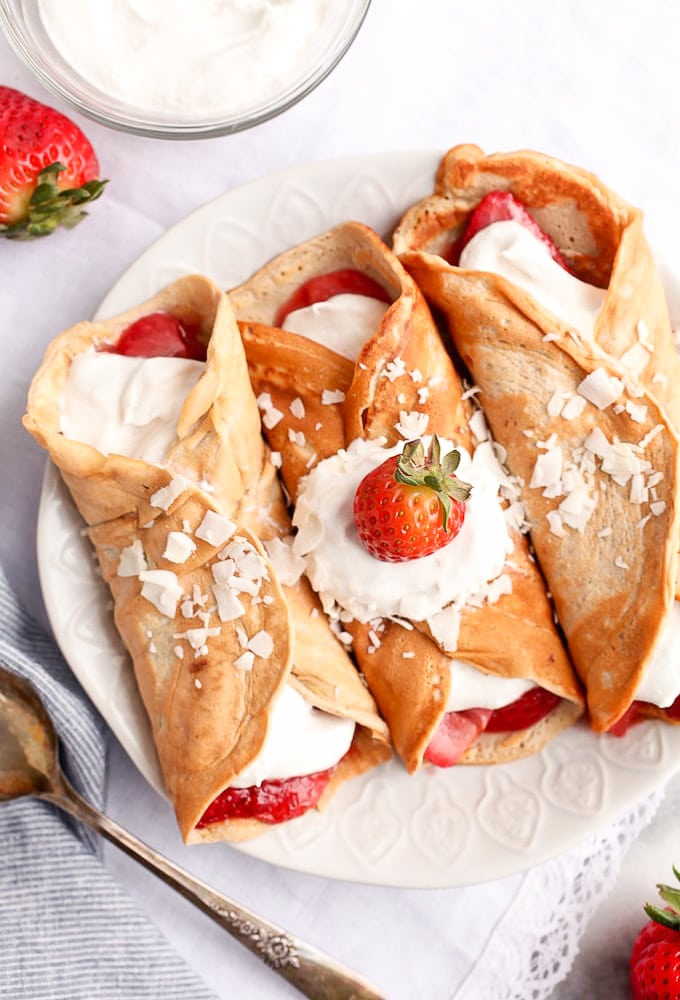 Healthy Protein Crepes on a plate topped with whipped cream and a strawberry