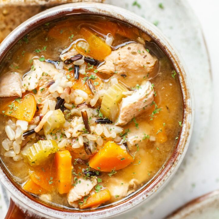 image of a close up of a bowl of instant pot chicken rice soup with carrots, celery, and thyme