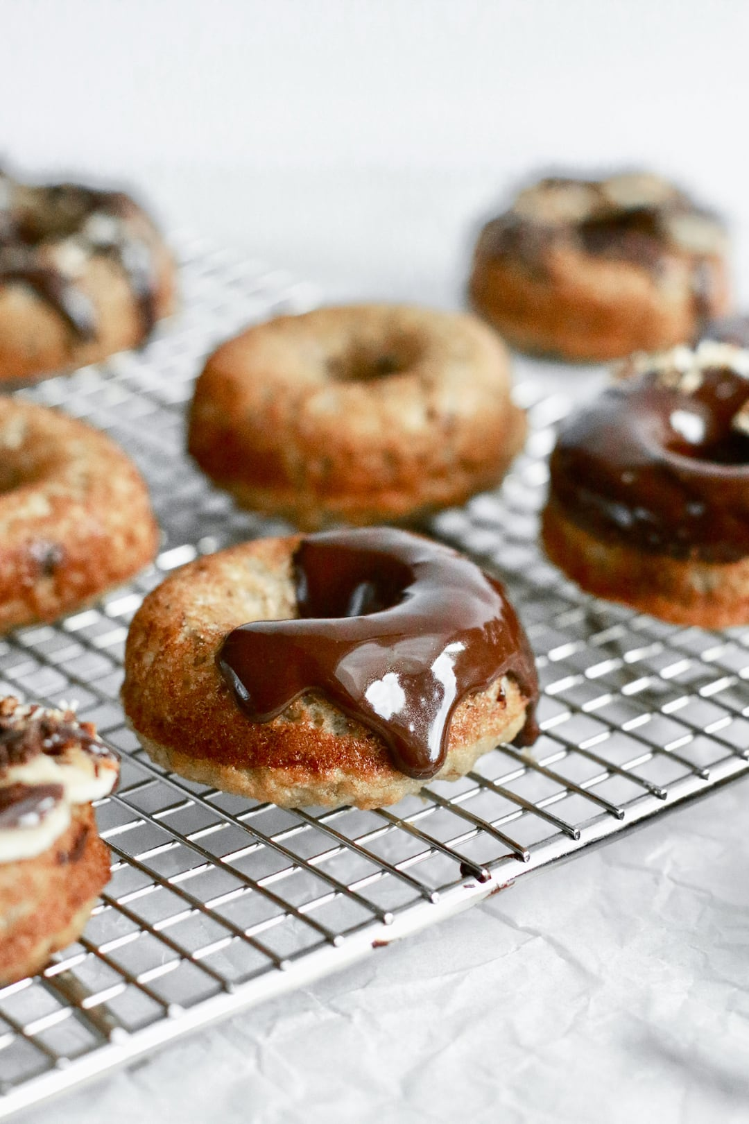Naturally sweetened chocolate glaze pouring over a healthy banana bread donut