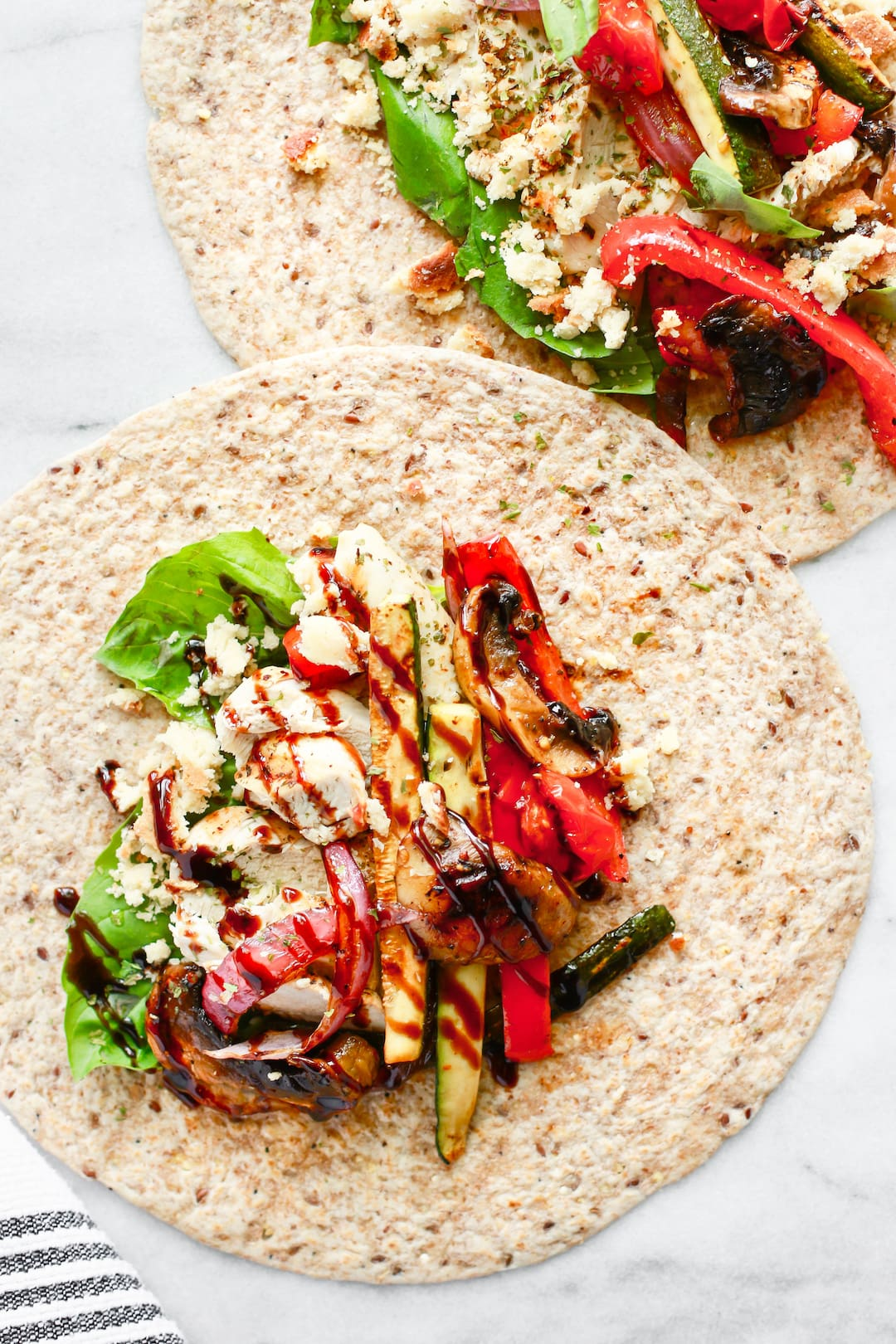 tortilla wraps with grilled vegetables, chicken, and a balsamic drizzle