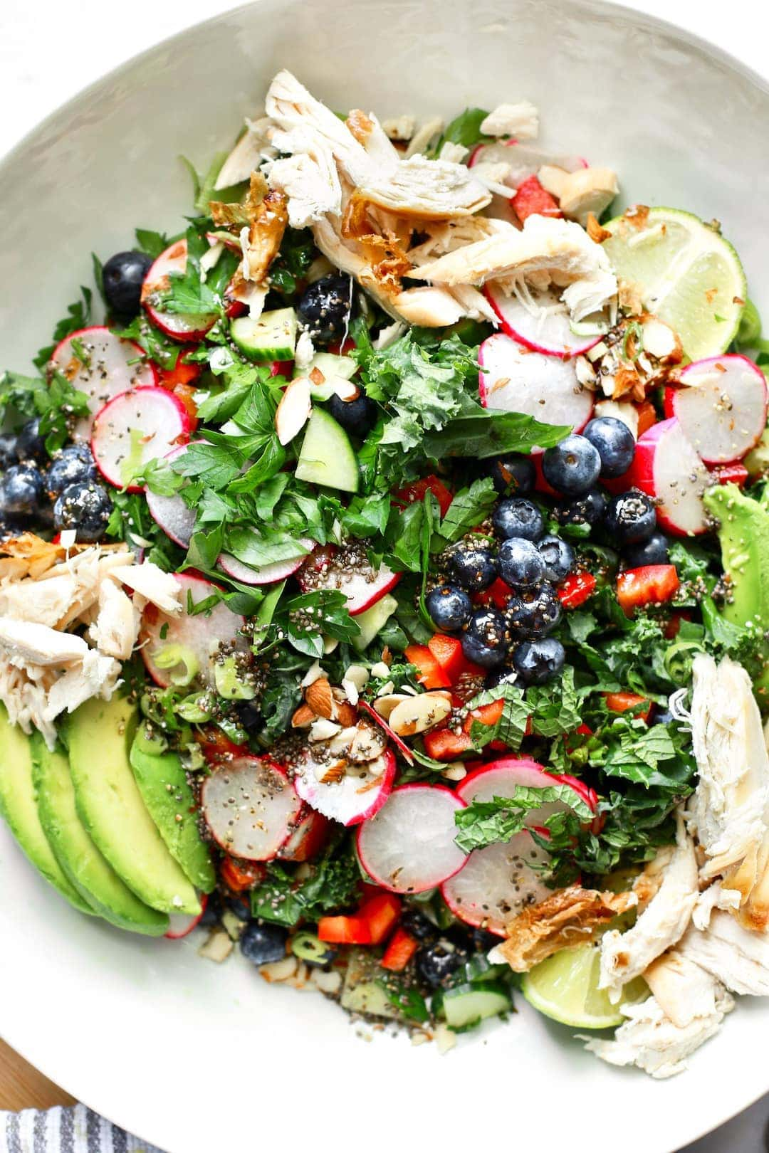 large salad bowl with bright vegetables, blueberries and chicken