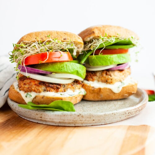 two turkey burgers with tomato, sprouts avocado, and onion