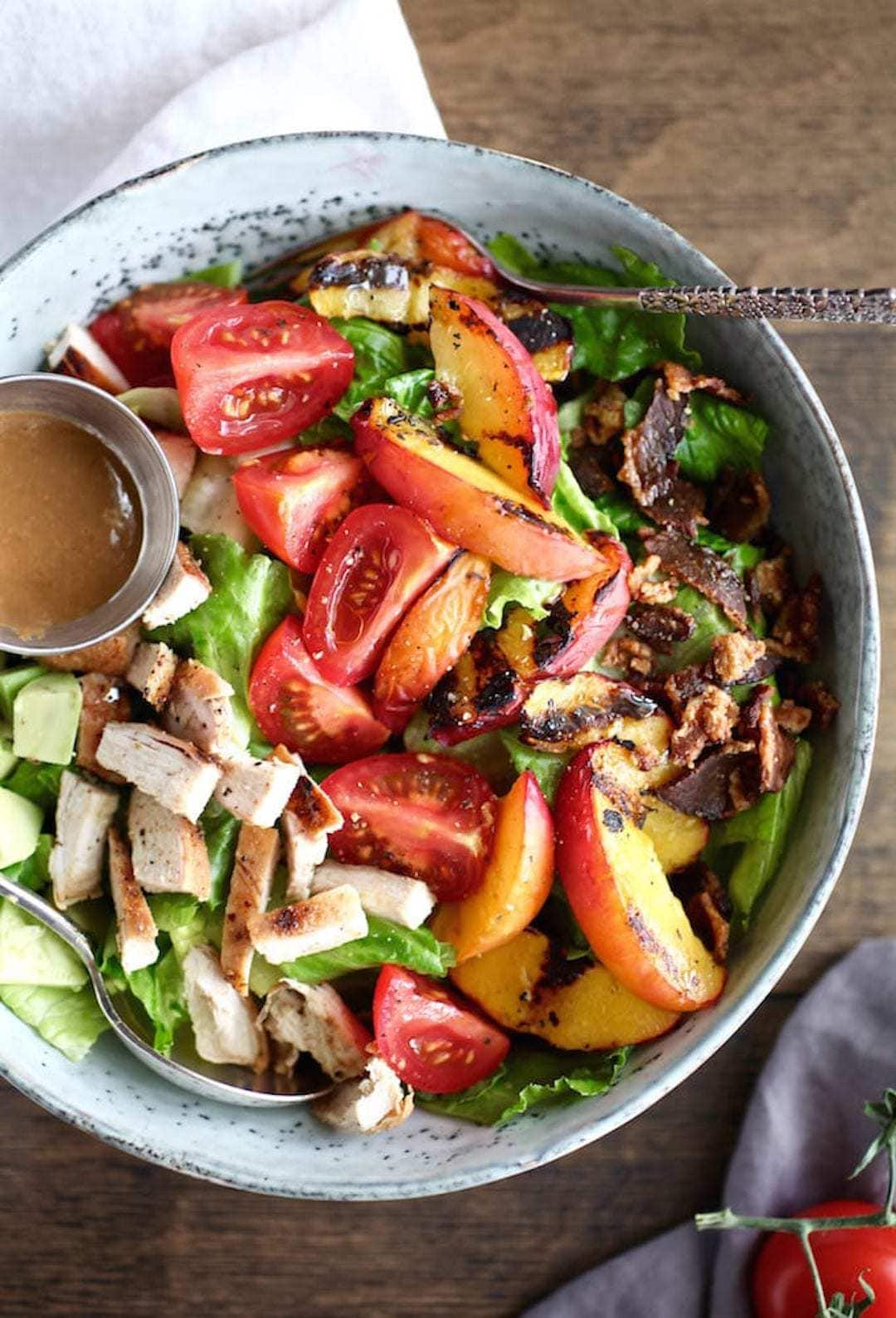 large bowl of salad with grilled chicken and nectarine