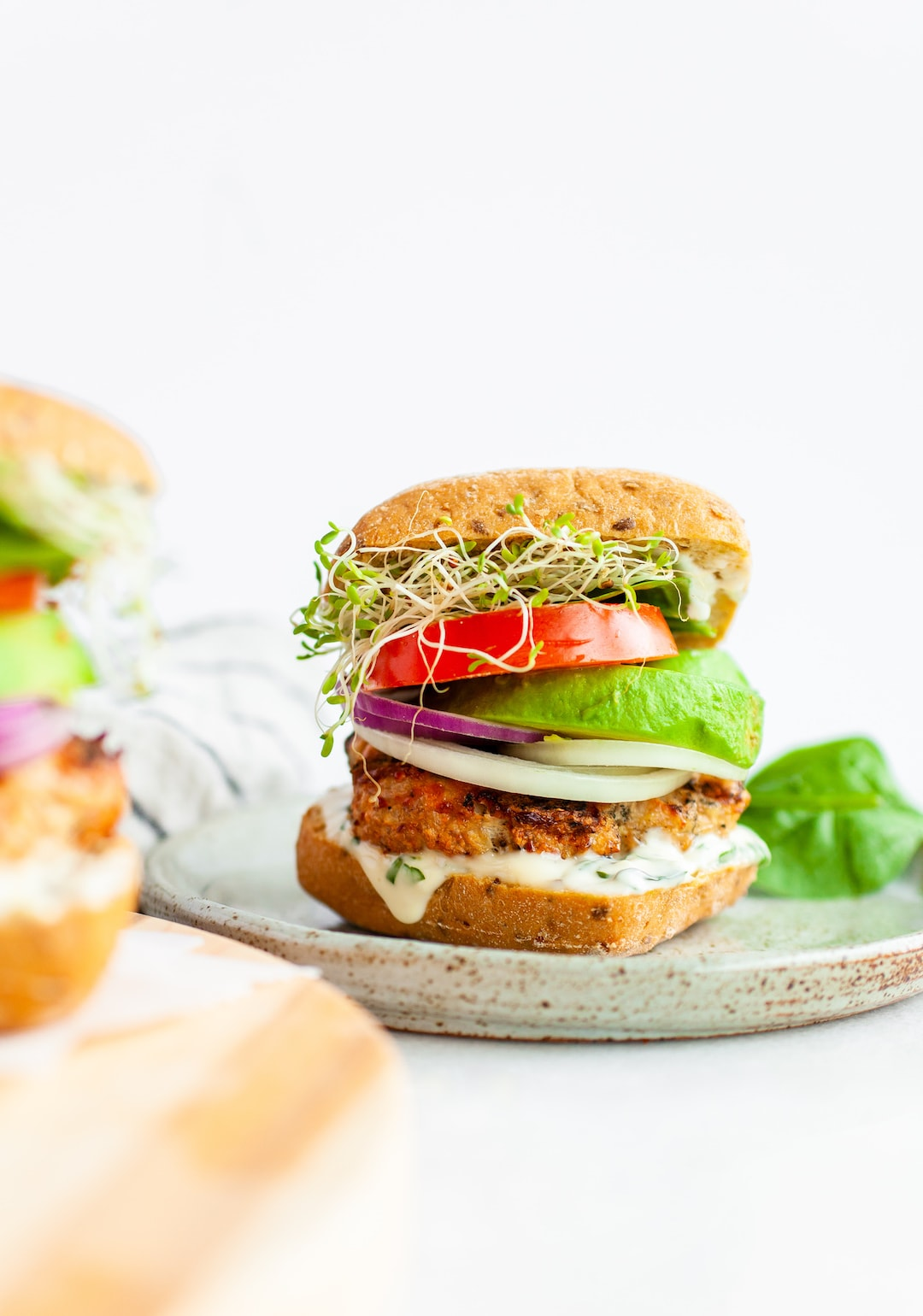 turkey burgers stacked with avocado, tomato, and sprouts on a grain bun
