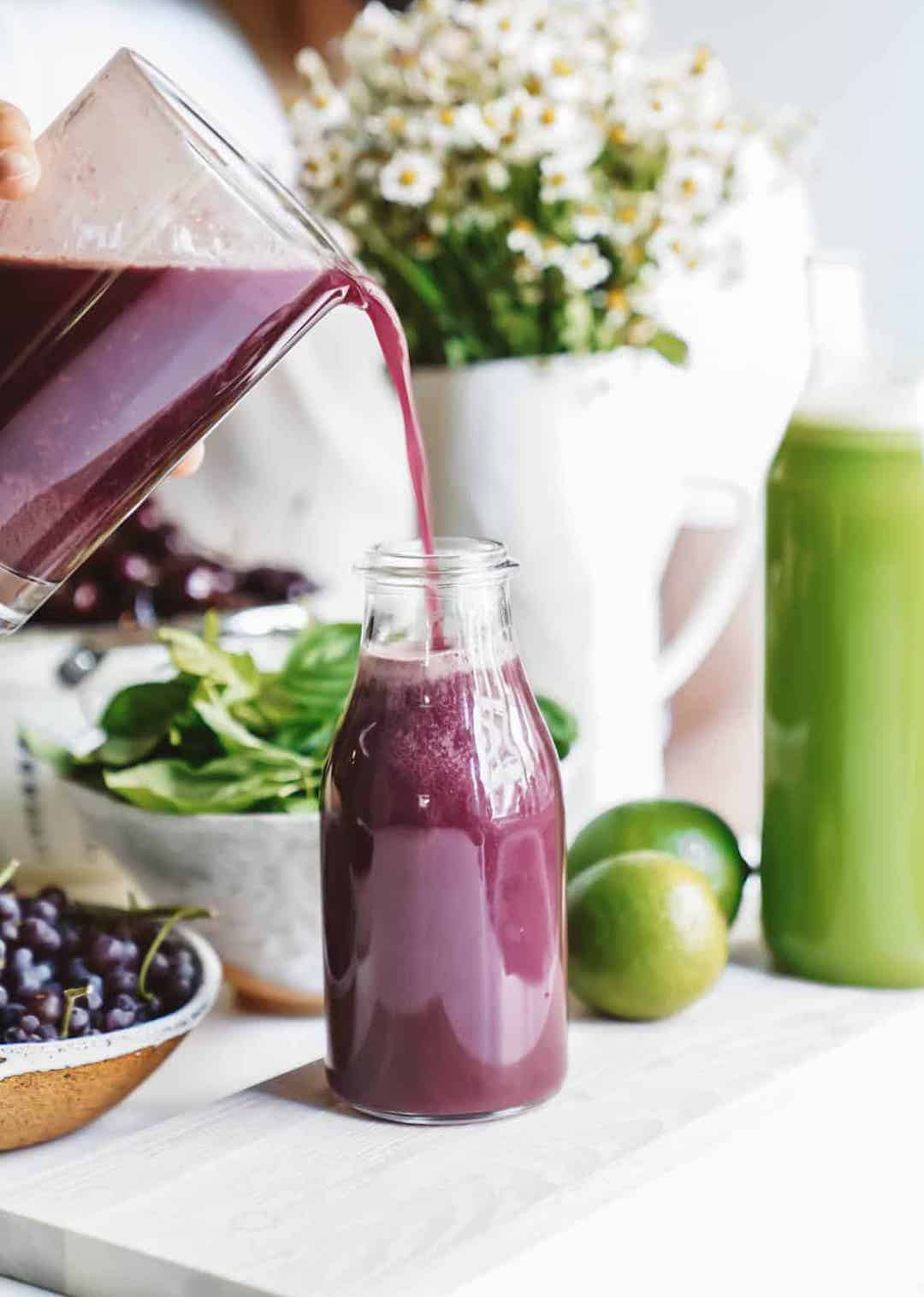 Pouring purple juice from a pitcher into a jar