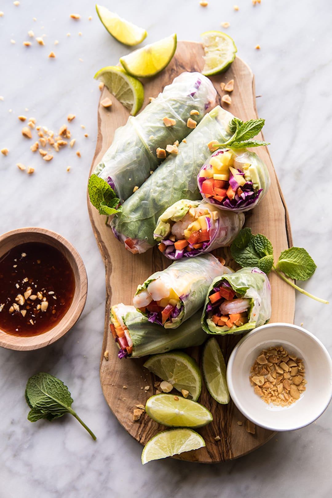 summer salad rolls with dip on a wood platter
