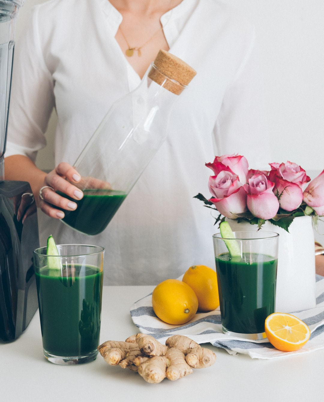 Woman with jug of dark green juice at a table with lemons