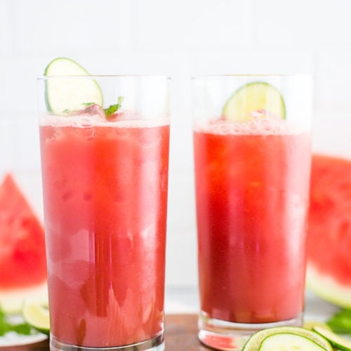 Two large glasses of watermelon juice with lime wedges