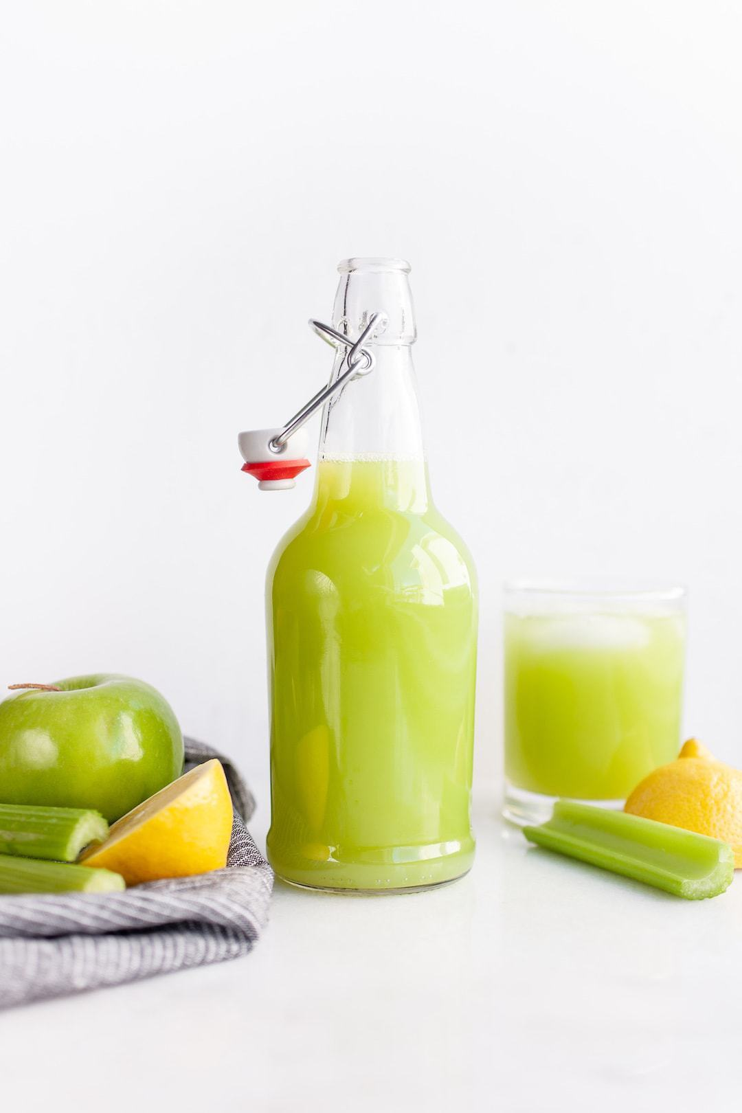 Jar of green celery juice with apples and celery on the side