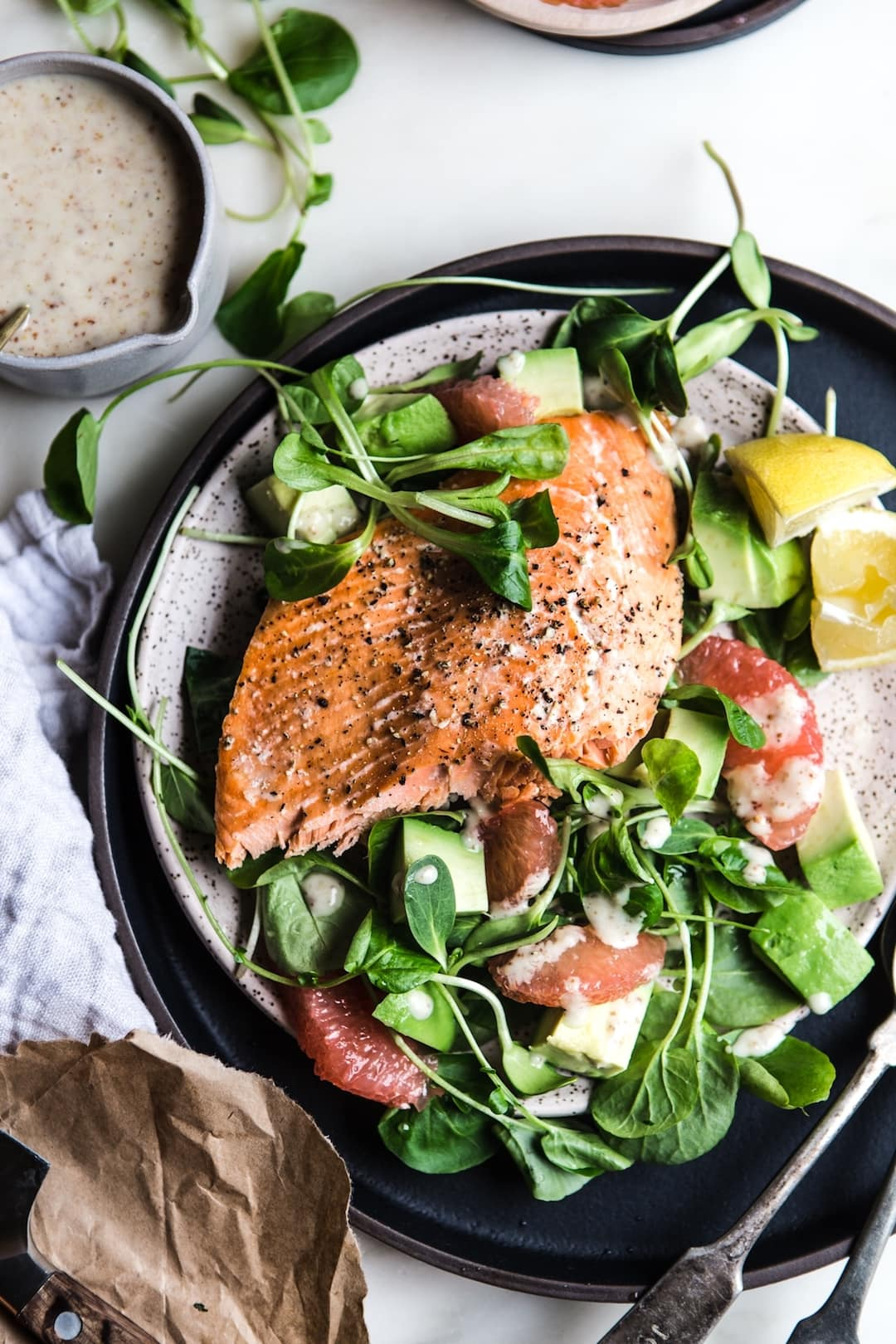 salmon salad on a large plate with dressing