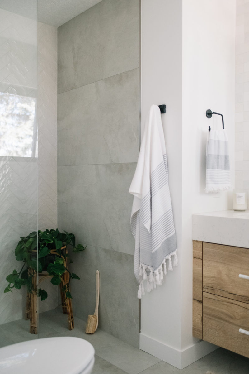 glass shower with grey tile and wood vanity