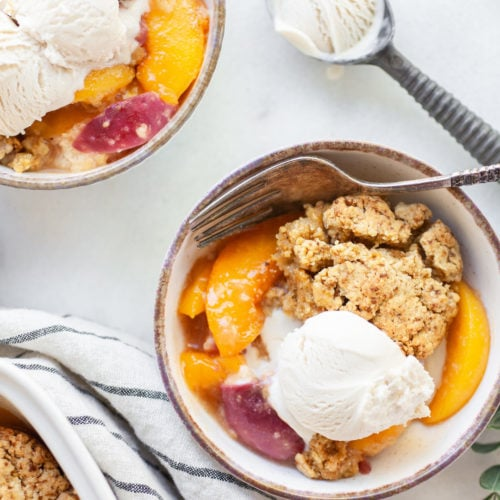 Bowl of peach cobbler and vanilla ice cream with a spoon and ice cream scoop on the side