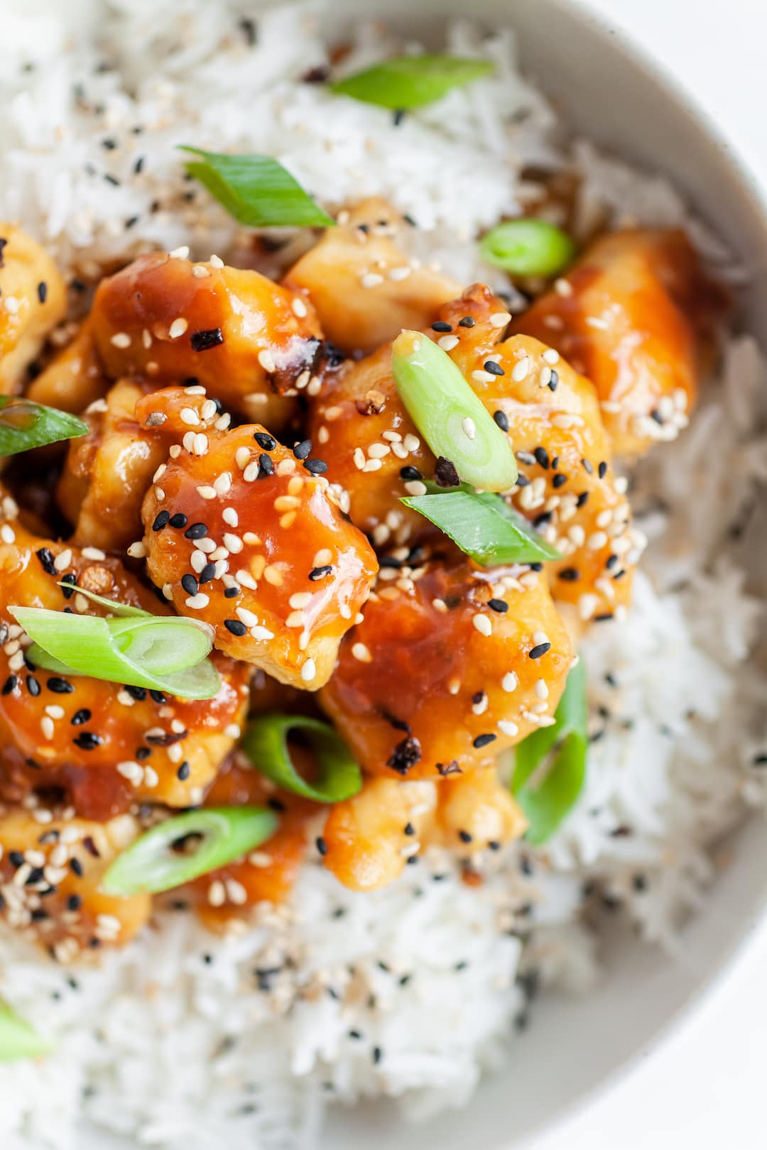 close up of orange chicken with sesame seeds and green onion