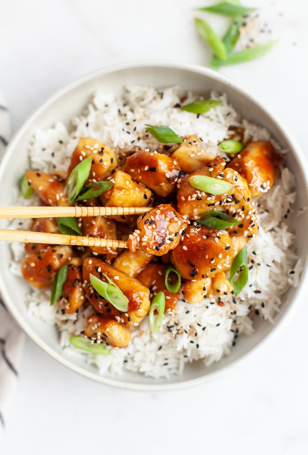 orange chicken in a bowl with chopstick