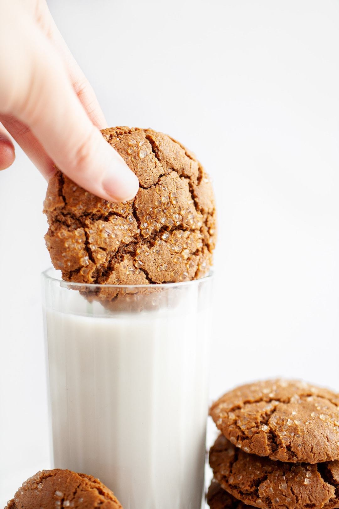 dipping ginger molasses cookie into a glass of milk