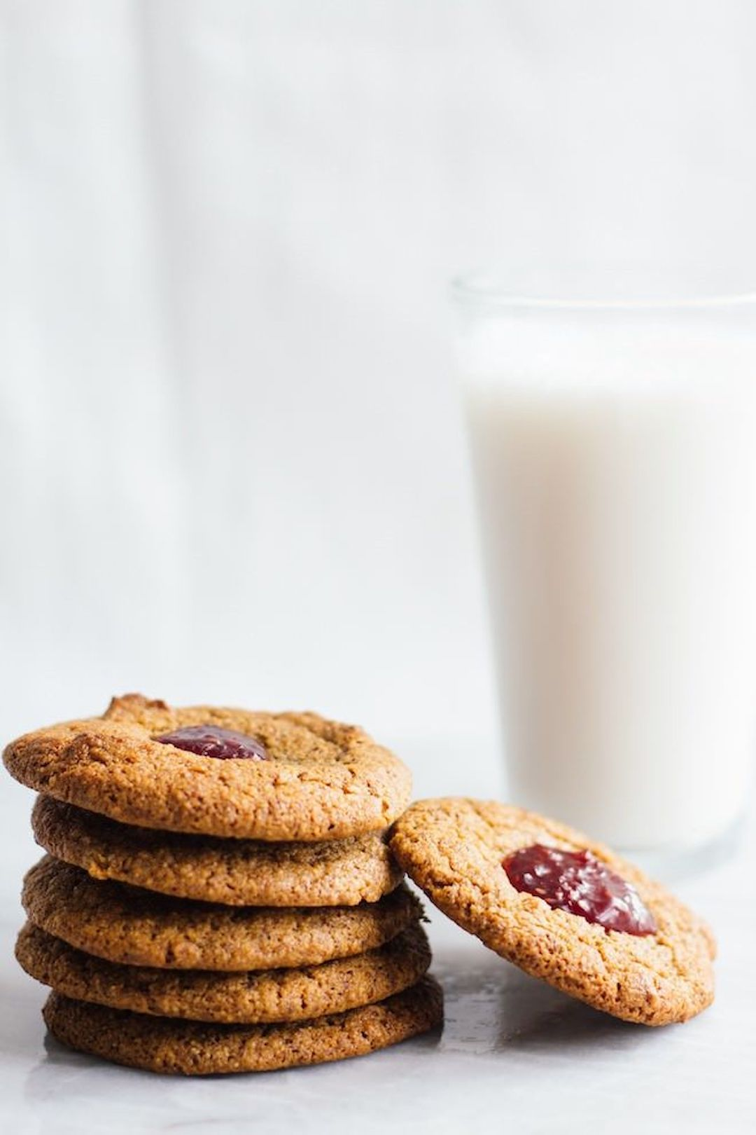 stacks of jam thumbprint cookies and a glass of milk