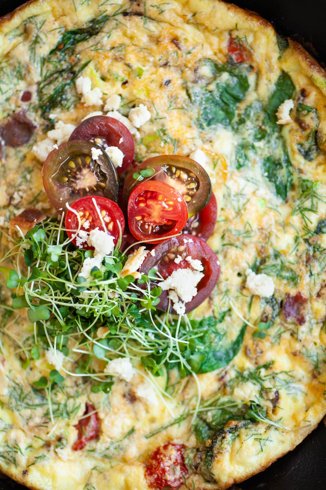 Close up of dairy free frittata topped with tomatoes and micro greens