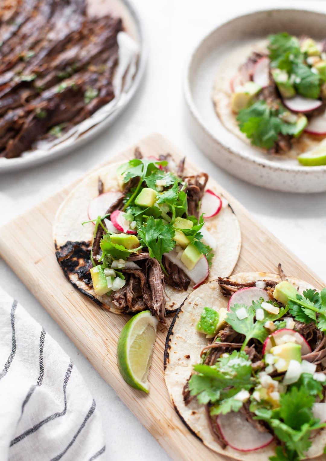 Crockpot Carne Asada tacos on wood tray