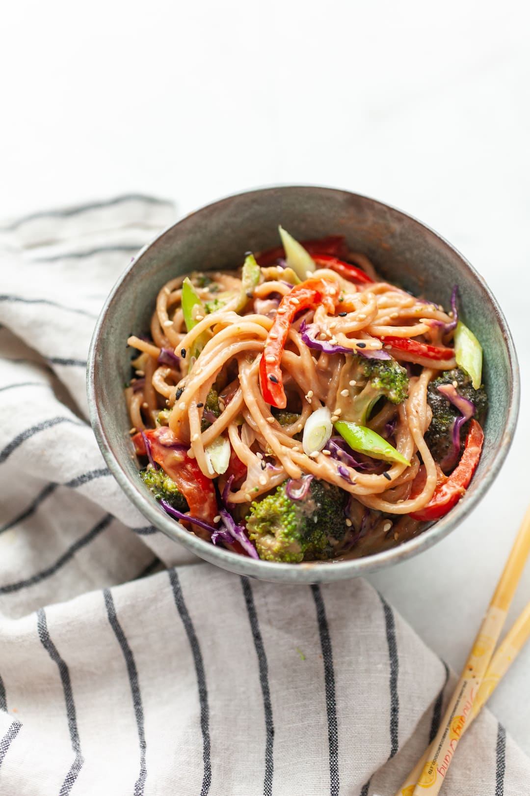 Bowl of peanut sauce noodles with vegetables and sesame seeds