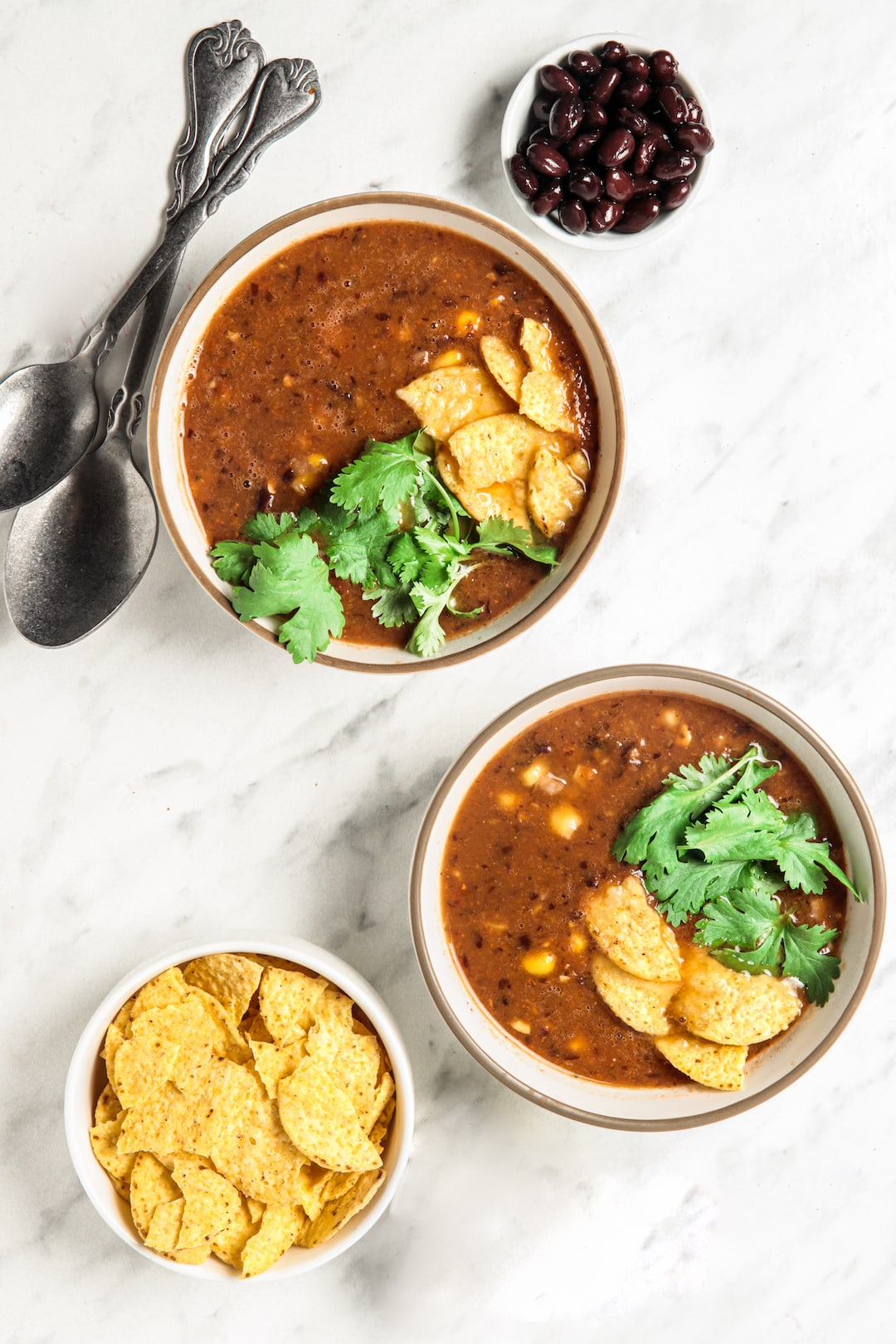 Two bowls of Easy Blender Vitamix Tortilla Soup with corn tortilla chips and cilantro garnish