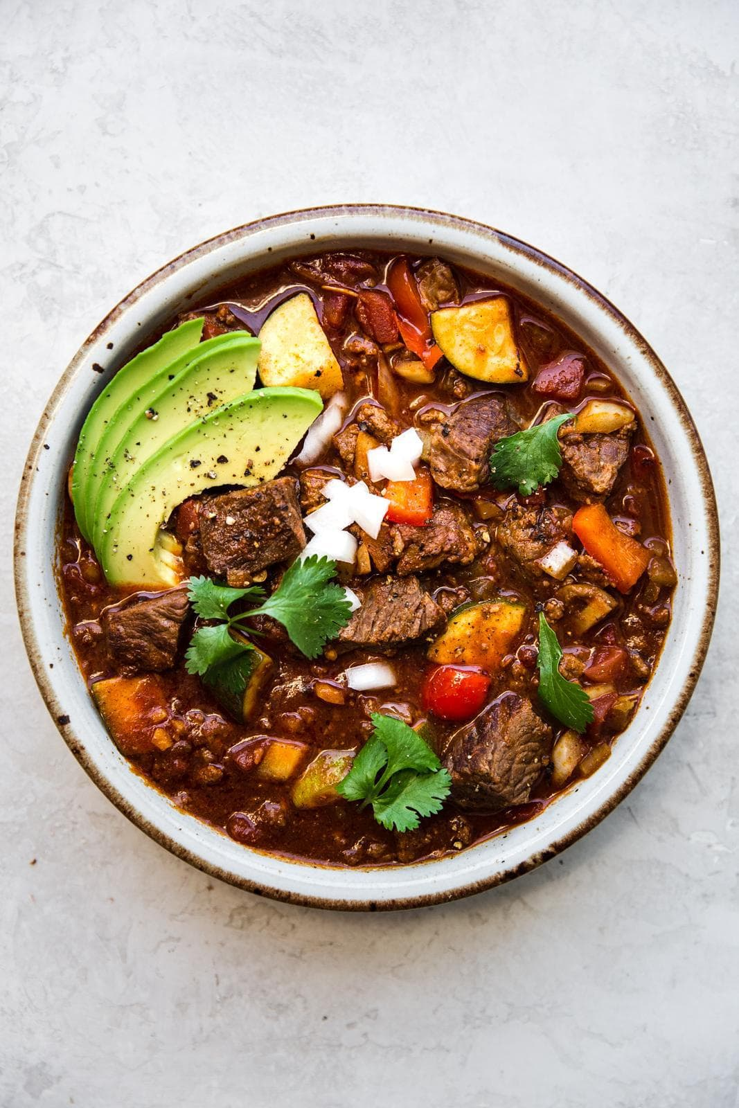 Bowl of crockpot paleo chili garnished with avocado