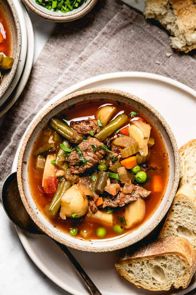Crockpot Vegetable Beef Soup in a bowl with bread on the side