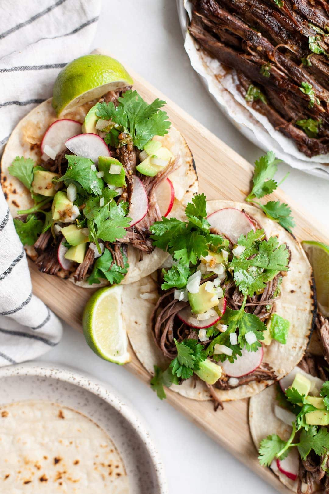 Two tacos filled with crockpot carne asada beef garnished with cilantro