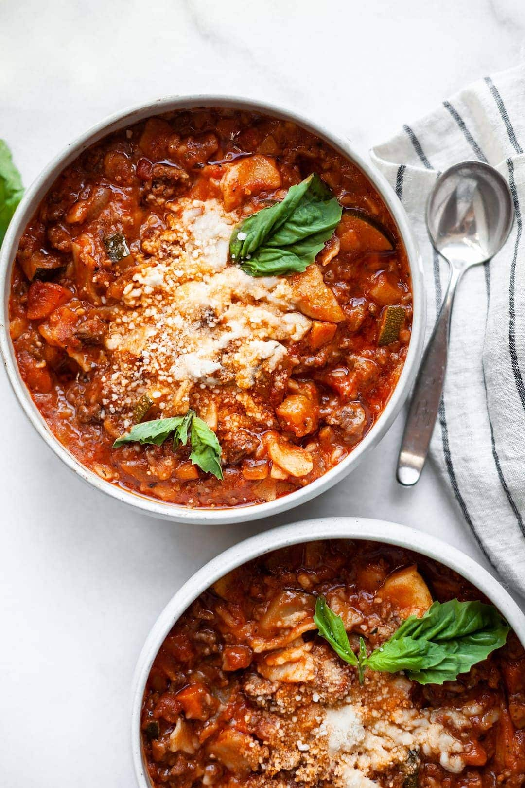 Slow Cooker Lasagna Soup in two bowls garnished with basil