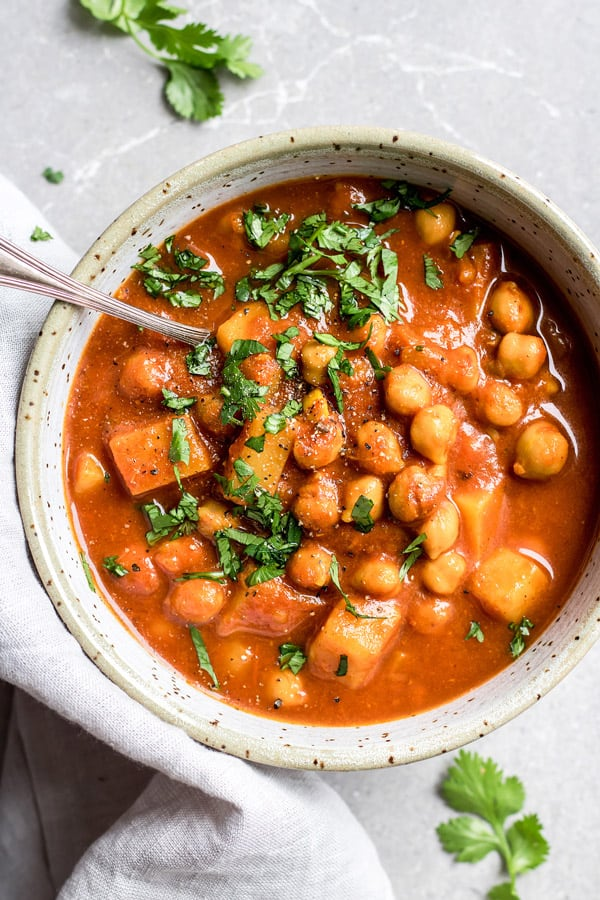 Colourful bowl of Moroccan chickpea stew garnished with fresh herbs