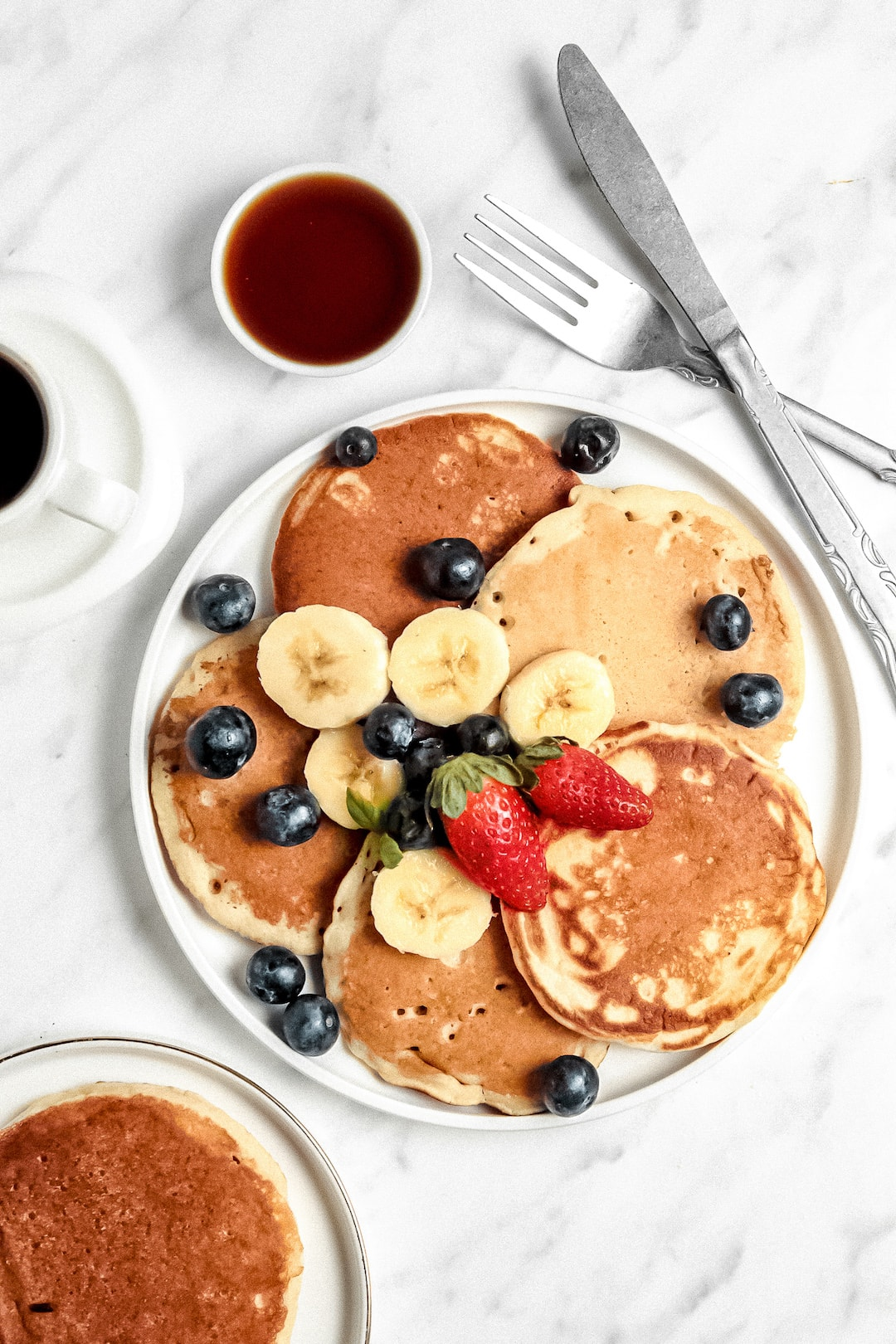 Overhead view of Healthy Cassava Flour Pancakes on a plate with strawberries and blueberries