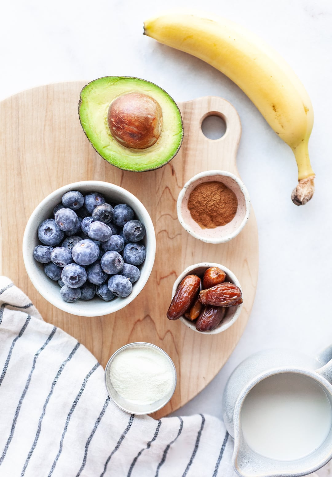 Flatlay of Creamy Blueberry Avocado Smoothie ingredients - blueberries, dates, avocado, cinnamon, banana, protein powder on a wood platter