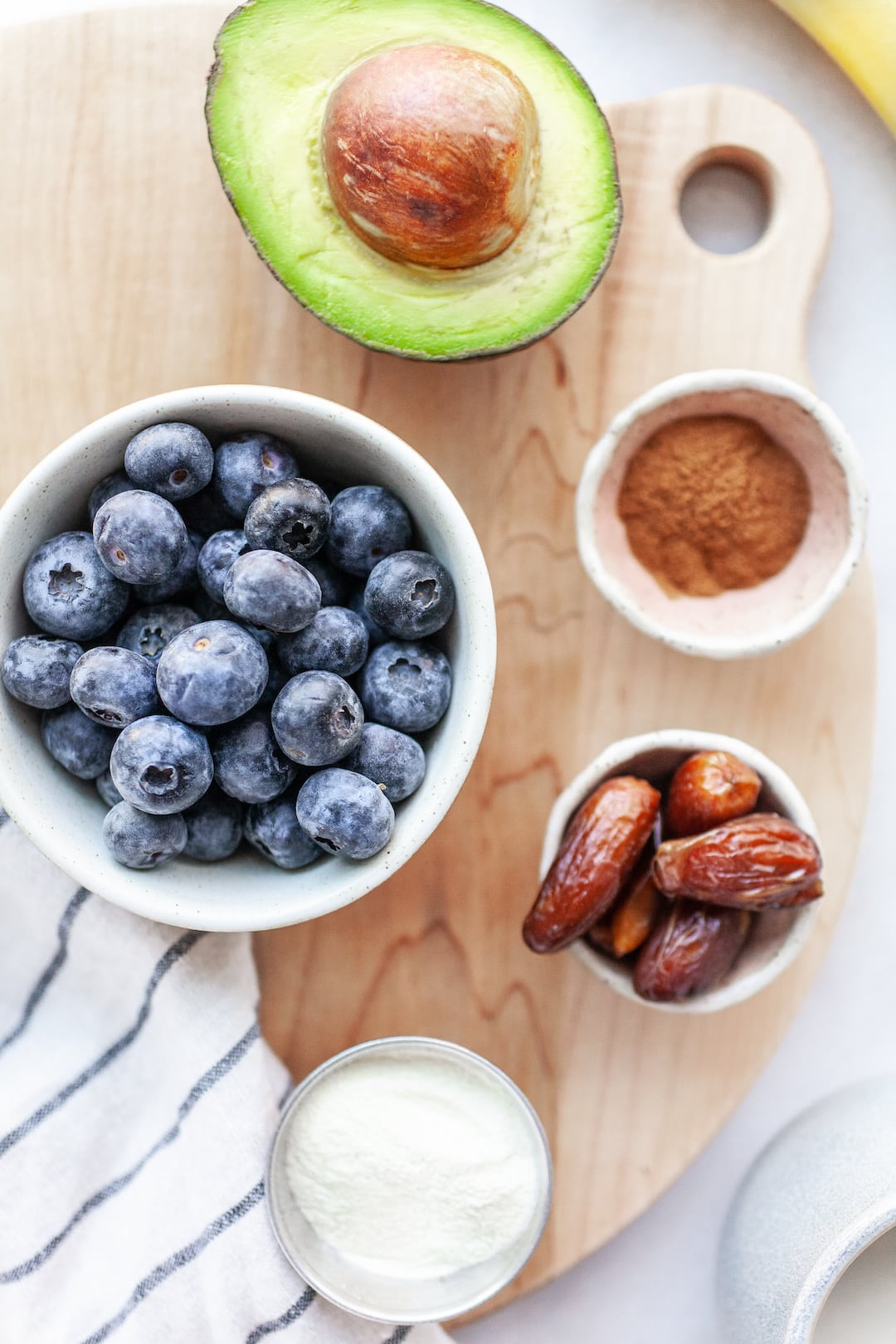 Flatlay of Creamy Blueberry Avocado Smoothie ingredients - blueberries, dates, avocado, cinnamon, banana, protein powder
