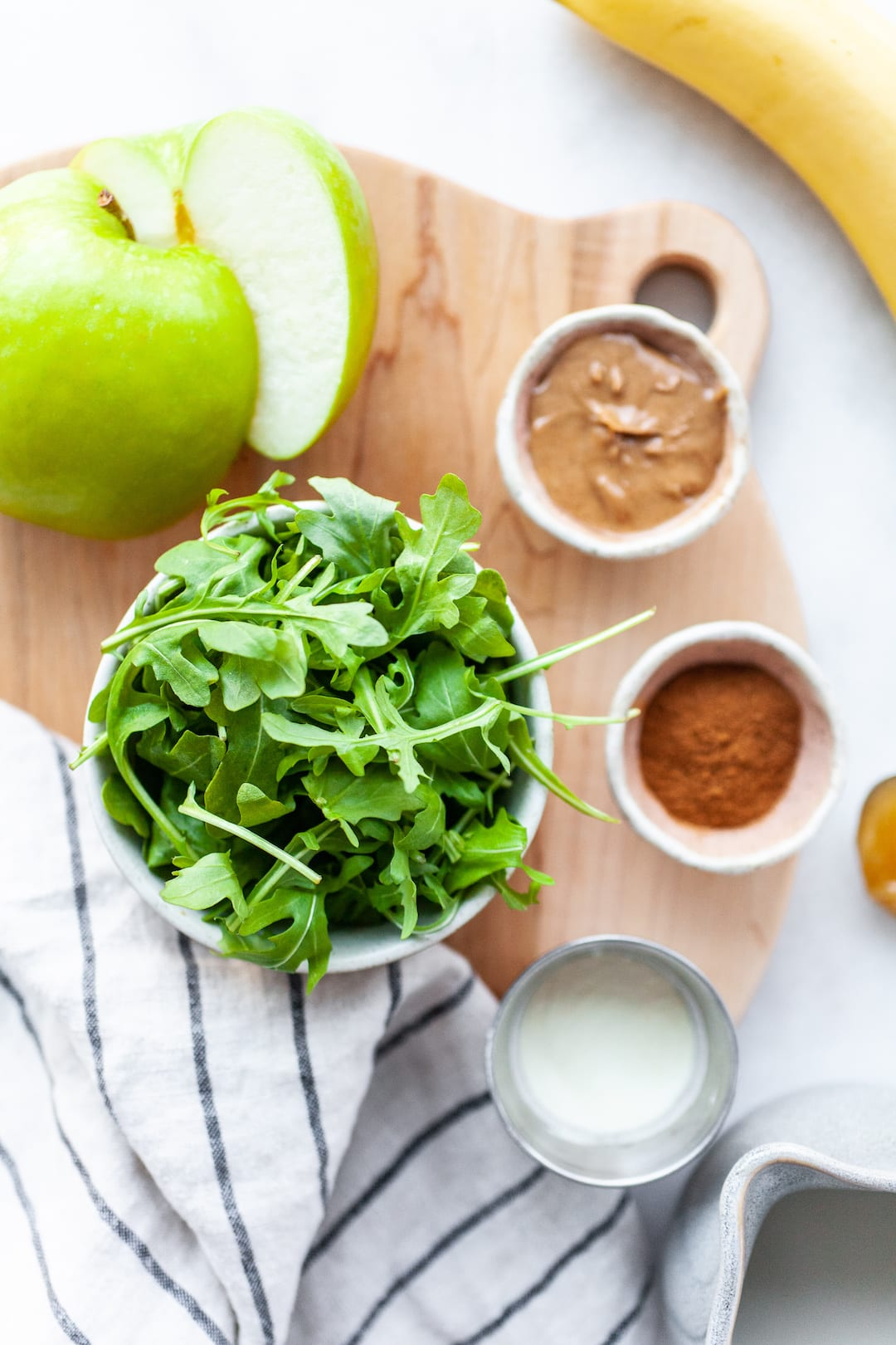 Ingredients for Delicious Arugula Smoothie Recipe spread out on a table