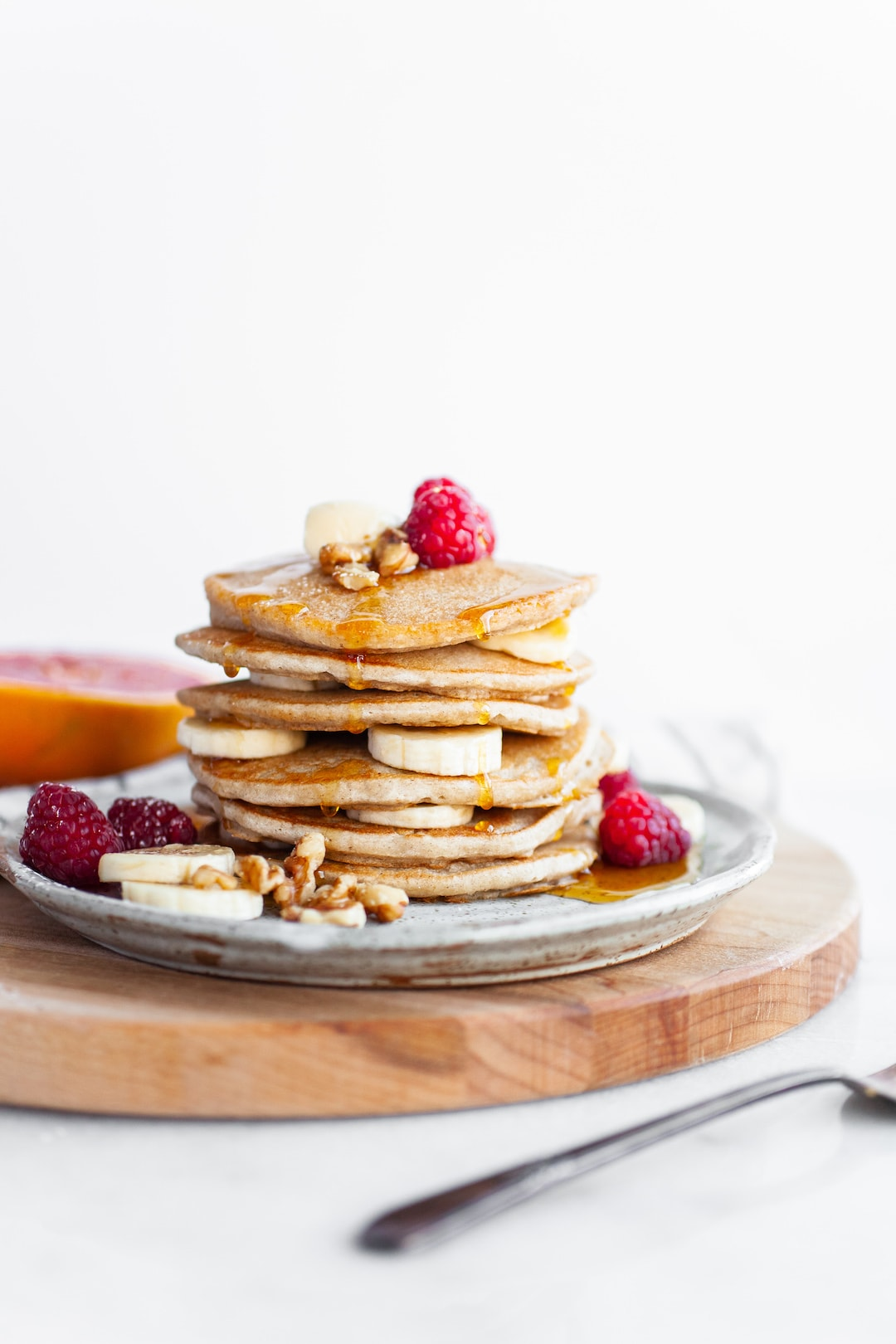 Perfect Vegan Buckwheat Pancakes stacked on a plate with raspberries and sliced banana