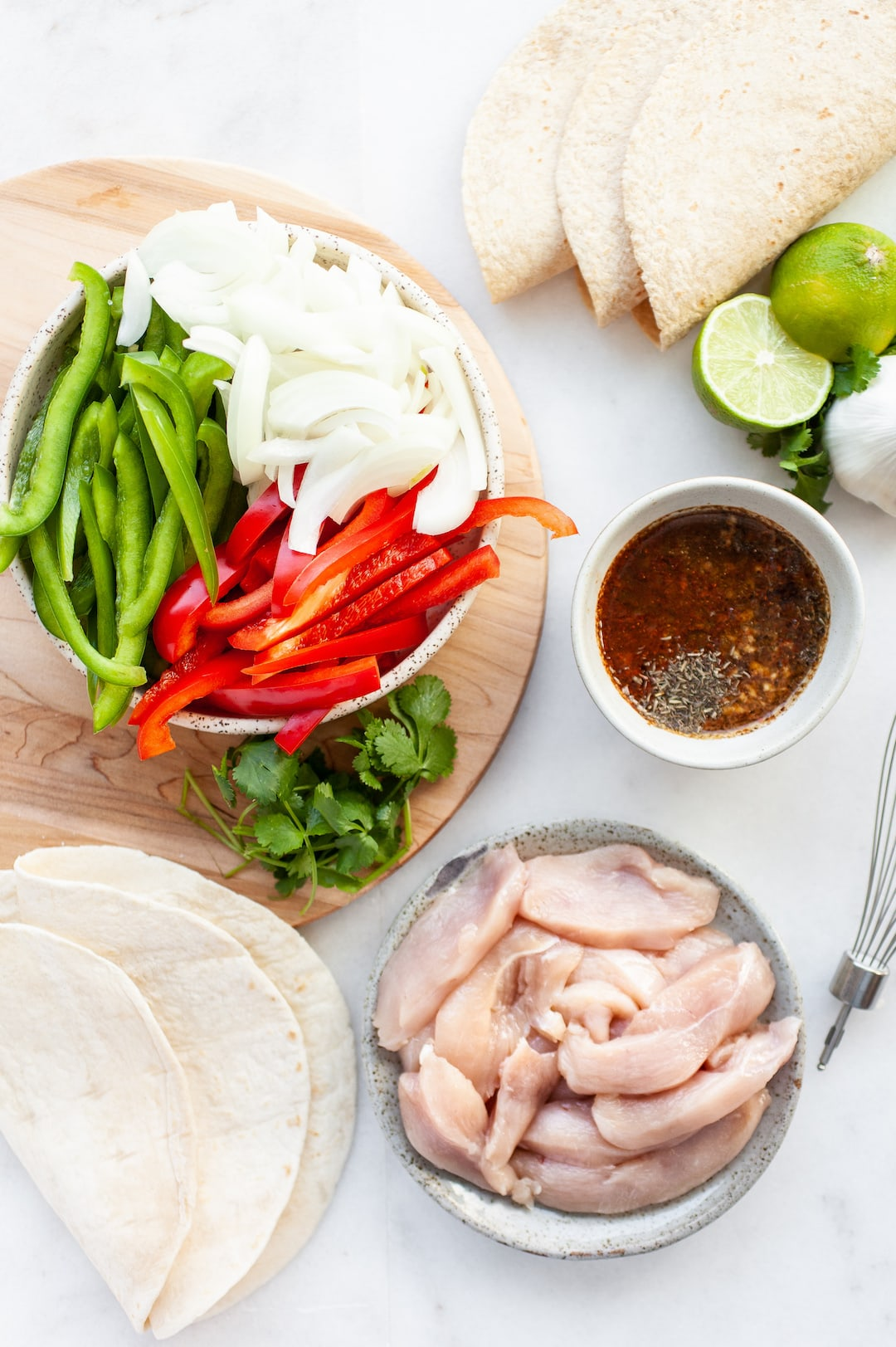 Flatlay of Instant Pot Chicken Fajitas ingredients - sauce, chicken, peppers, onion, lime, fajitas