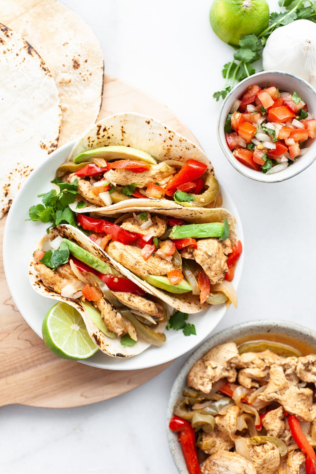 Instant Pot Chicken Fajitas on a plate with fresh salsa, avocado, and lime
