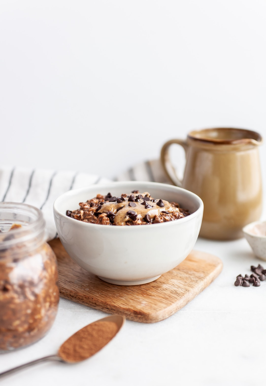 Healthy Chocolate Overnight Oats in a white bowl on a wood tray