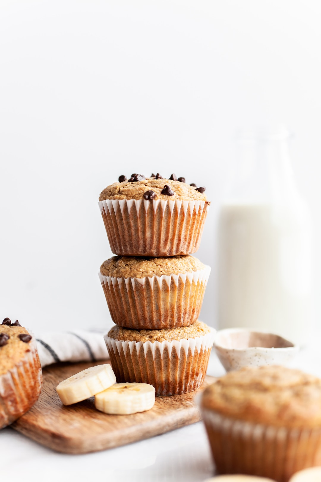 Stack of three Easy Almond Flour Banana Muffins with glass of milk in the background