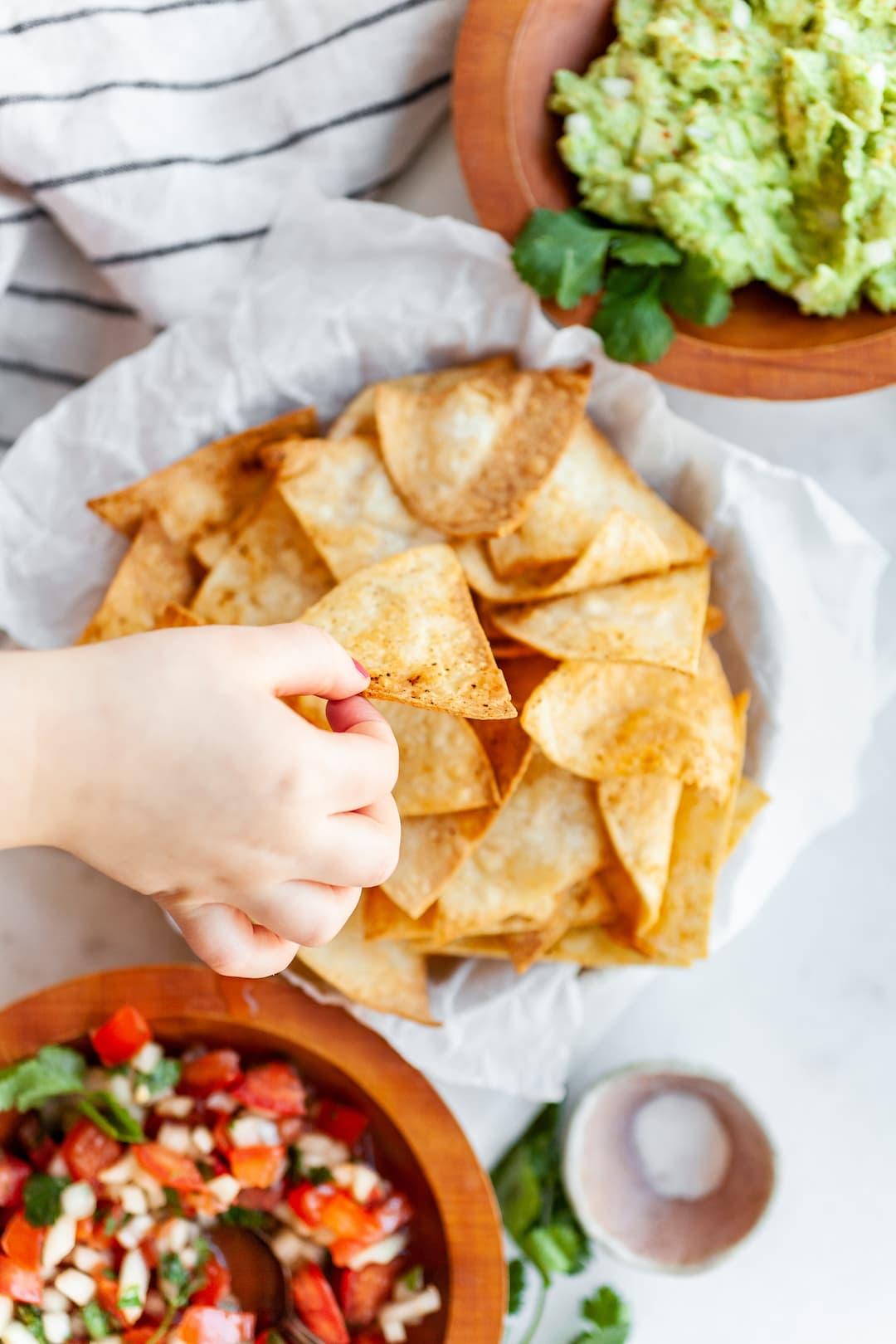 Hand grabbing an air fryer tortilla chip from a platter with guacamole, salsa, and air fryer tortilla chips