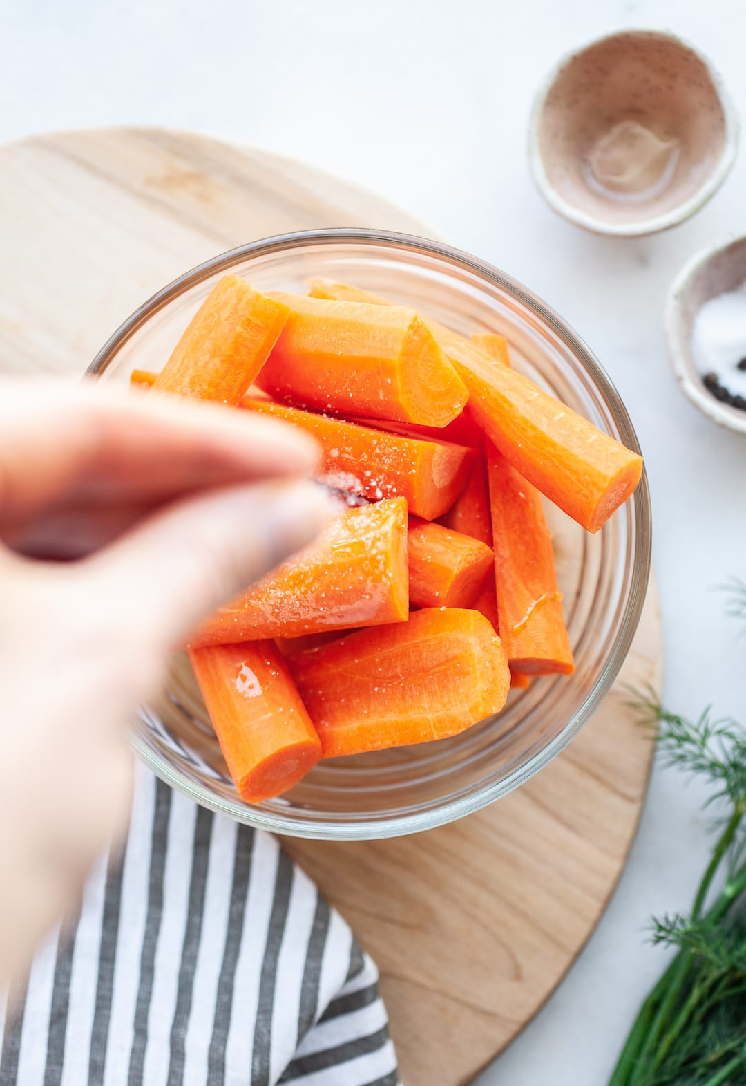 raw carrots in a glass bowl sprinkled with sea salt