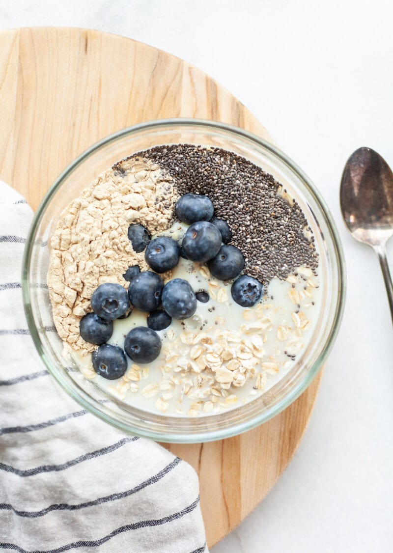 Making blueberry overnight oats in a glass bowl