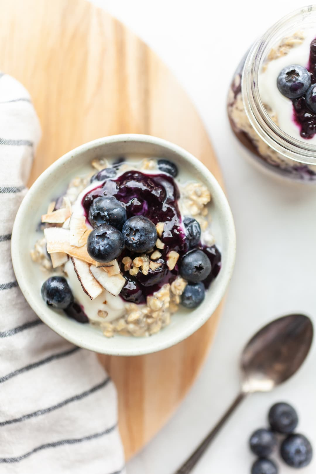 Bowl and jar of blueberry overnight oats on a wood tray with a white background